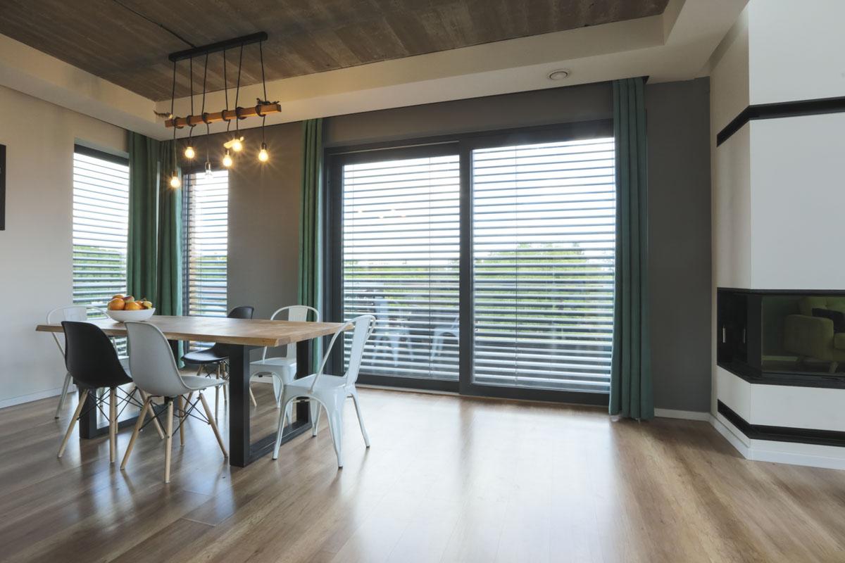 Żaluzje zewnętrzne zamontowane na dużych oknach zapewniają prywatność domownikom.