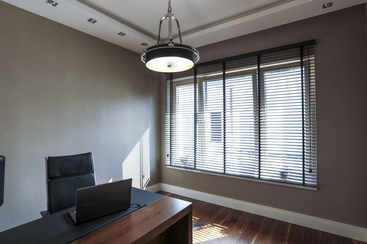 Żaluzje metalowe perforowane blokują uciążliwe promienie słoneczne bez przesłaniania widoków za oknem.